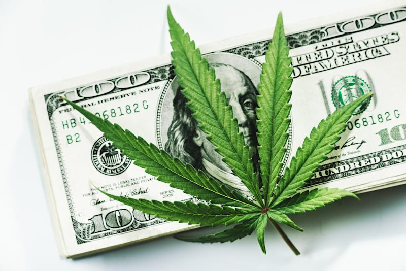 A cannabis leaf on top of a pile of one hundred dollar bills.