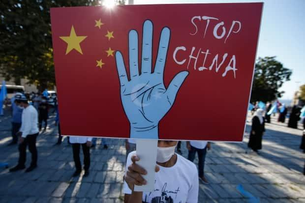 A protester from the Uighur community in Turkey holds an anti-China placard during a protest in Istanbul in October.