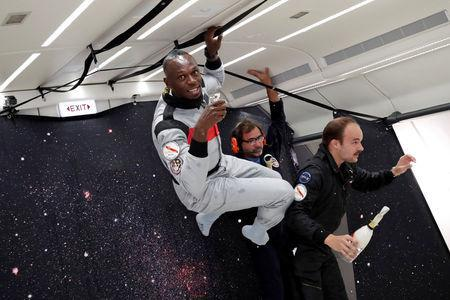 """Retired sprinter Usain Bolt and French Interior designer Octave de Gaulle who designed a bottle of """"Mumm Grand Cordon Stellar"""" champagne enjoy zero gravity conditions during a flight in a specially modified Airbus Zero-G plane above Reims, France, September 12, 2018. REUTERS/Benoit Tessier"""