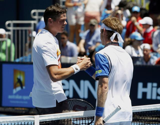 Milos Raonic (L) of Canada shakes hands with Daniel Gimeno-Traver of Spain after winning their men's singles match at the Australian Open 2014 tennis tournament in Melbourne January 14, 2014. REUTERS/Brandon Malone (AUSTRALIA - Tags: SPORT TENNIS)