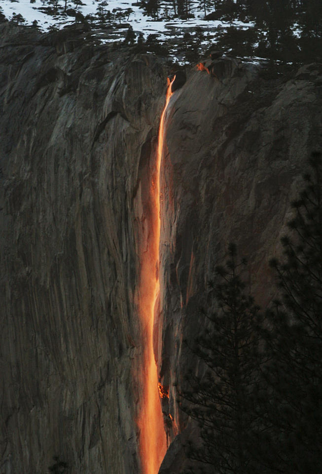 "FILE - In this Feb. 16, 2010, file photo, a shaft of sunlight creates a glow near Horsetail Fall, in Yosemite National Park, Calif. Mother Nature is again putting on a show at California's Yosemite National Park, where every February the setting sun draws a narrow sliver on a waterfall to make it glow like a cascade of molten lava. The phenomenon known as ""firefall"" draws scores of photographers to the spot, which flows down the granite face of the park's famed rock formation, El Capitan. (Eric Paul Zamora/The Fresno Bee via AP, File)"