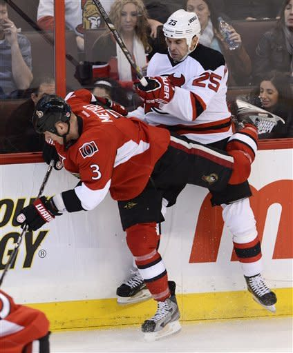 New Jersey Devils right wing Tom Kostopoulos collides with Ottawa Senators defenseman Marc Methot along the boards during second period NHL action in Ottawa, on Monday March 25, 2013. (AP Photo/The Canadian Press, Adrian Wyld)