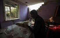 Local resident Sakit Orucov is seen in his house that was allegedly damaged by recent shelling during the fighting over the breakaway region of Nagorno-Karabakh, in the city of Tartar