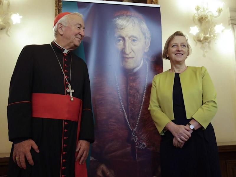 Cardinal Vincent Nichols and Sally Jane Axworthy, the British Ambassador to the Holy See, stand in front of picture of Cardinal John Henry Newman ahead of his upcoming canonisation: AP