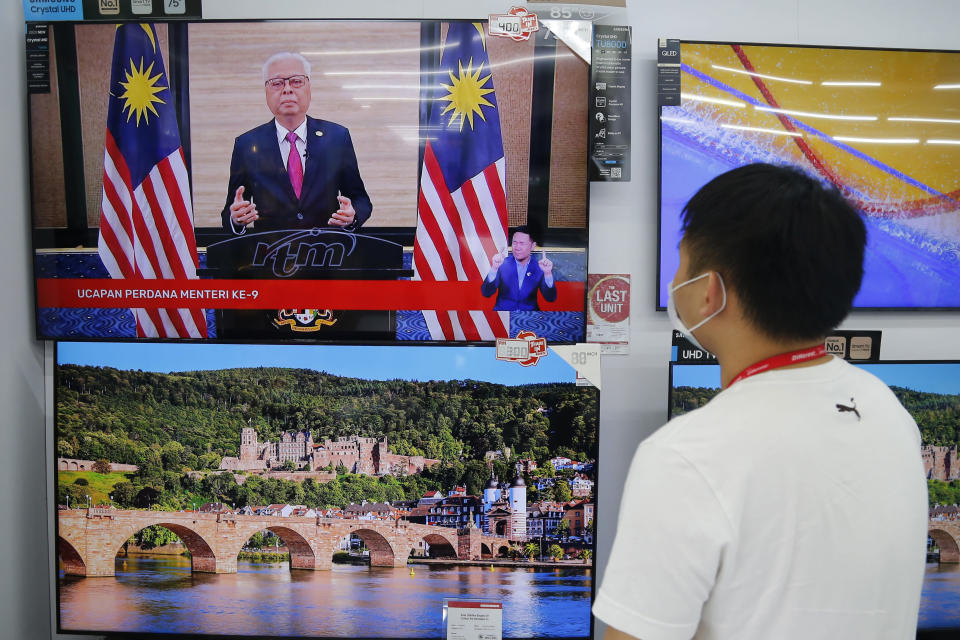 An electronic shop worker watches a speech by Malaysia's new Prime Minister Ismail Sabri Yaakob on television in Shah Alam, Malaysia, Sunday, Aug. 22, 2021. Ismail struck a conciliatory tone in his first national address Sunday, saying he would embrace the opposition in efforts to tackle a runaway pandemic and revive a slumping economy. (AP Photo/Lai Seng Sin)