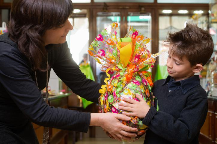 A child is handed a wrapped Easter egg in a store.