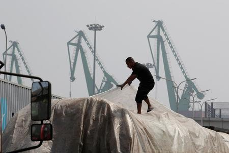 A labourer works outside a logistics center near Tianjin Port, in northern China, May 16, 2019. REUTERS/Jason Lee