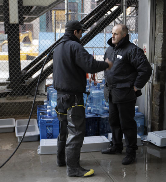 A worker wearing hip boots talks to a co-worker outside the World Trade Center memorial site as work continues to get the September 11 Memorial cleaned up after it was closed by flooding in the wake of Superstorm Sandy, Monday, Nov. 5, 2012, in New York. Joe Daniels, president of the September 11 Memorial and Museum, said Monday that water that rushed into the site has been pumped out and the memorial will re-open Tuesday. (AP Photo/Kathy Willens)