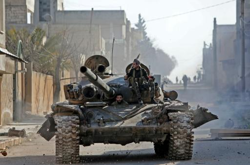A rebel tank patrols the streets of Saraqeb, reduced to a ghost town abandoned by its residents after weeks of fighting