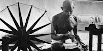 Mohandas Karamchand Gandhi reading as he sits cross-legged on floor next to a spinning wheel which looms in the foreground as a symbol of India's struggle for Independence, at home. Photo: Margaret Bourke-White/Time & Life Pictures/Getty Images