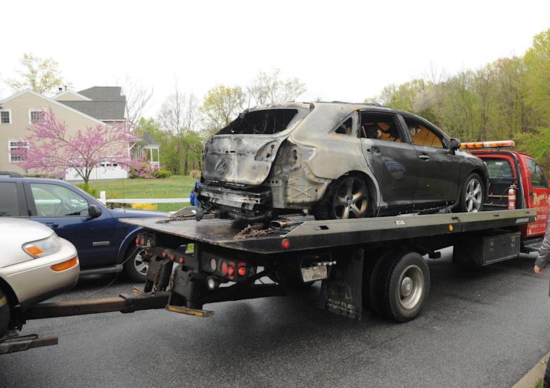 Two vehicles, one  badly burnt out is removed from the scene of the house fire on Tuesday, May 1, 2012, in Carmel, N.Y.    A police captain, his wife and two teenage daughters died in a fire that swept through their home early Tuesday.  Larchmont, N.Y. police identified the dead as Thomas Sullivan of the Larchmont police, his wife, Donna, and their two daughters. A son escaped from the burning Carmel home in Putnam County, about 60 miles north of New York City. (AP Photo/Louis Lanzano)