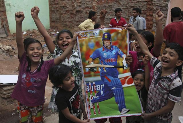Indian cricket fans hold a poster of Sachin Tendulkar and cheer as they gather to honor him in Hyderabad, India, Wednesday, Nov. 13, 2013. Tendulkar will retire from international cricket after playing his 200th test match in Mumbai from Nov. 14-18. (AP Photo/ Mahesh Kumar A.)