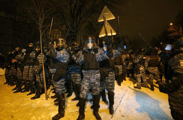 Riot police get ready to displace pro-European Union activists from their barricades at the Ukrainian presidential administration building in Kiev, Ukraine, Tuesday, Dec. 10, 2013. Heavily armed riot troops broke into the offices of a top Ukrainian opposition party in Kiev and seized its servers Monday, the party said, as anti-government protests crippled the capital for yet another day. Elsewhere police dismantled or blocked off several small protest tent camps set up near key national government buildings in the city. (AP Photo/Alexander Zemlianichenko)