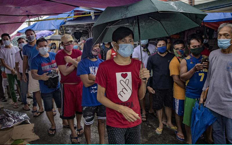 Filipinos hoping to go back home to their provinces but were left stranded after the government reimposed a coronavirus lockdown queue for free meals from volunteers as they wait outside the closed ticketing office of a ferry company - Ezra Acayan/Getty Images
