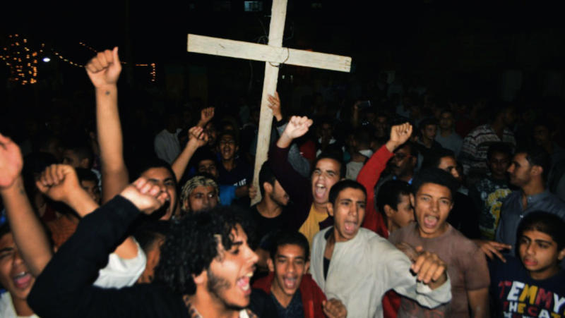 Coptic Christians chant slogans during a protest following an attack on a bus carrying Christian pilgrims on their way to a remote desert monastery, in Minya, Egypt, Friday, Nov. 2, 2018. Egypt's Coptic Orthodox Church and the Interior Ministry say Islamic militants have ambushed three buses carrying Christian pilgrims on their way to a remote desert monastery south of the Egyptian capital of Cairo, killing at least seven and wounding a dozen more. (AP Photo/Mohammed Hakim)