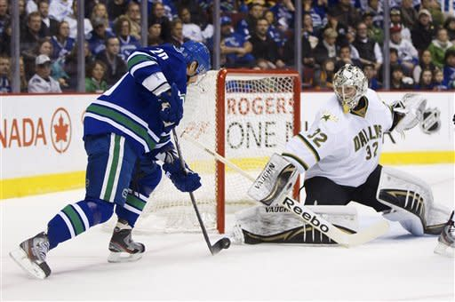 Dallas Stars goalie Kari Lehtonen, right, of Finland, stops Vancouver Canucks' Christopher Higgins during the first period of an NHL hockey game, Friday, March 30, 2012, in Vancouver, British Columbia. (AP Photo/The Canadian Press, Darryl Dyck)