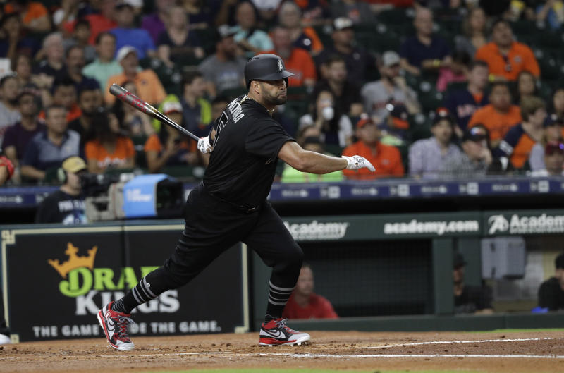 Los Angeles Angels' Albert Pujols hits an RBI single against the Houston Astros during the second inning of a baseball game Friday, Aug. 23, 2019, in Houston. (AP Photo/David J. Phillip)