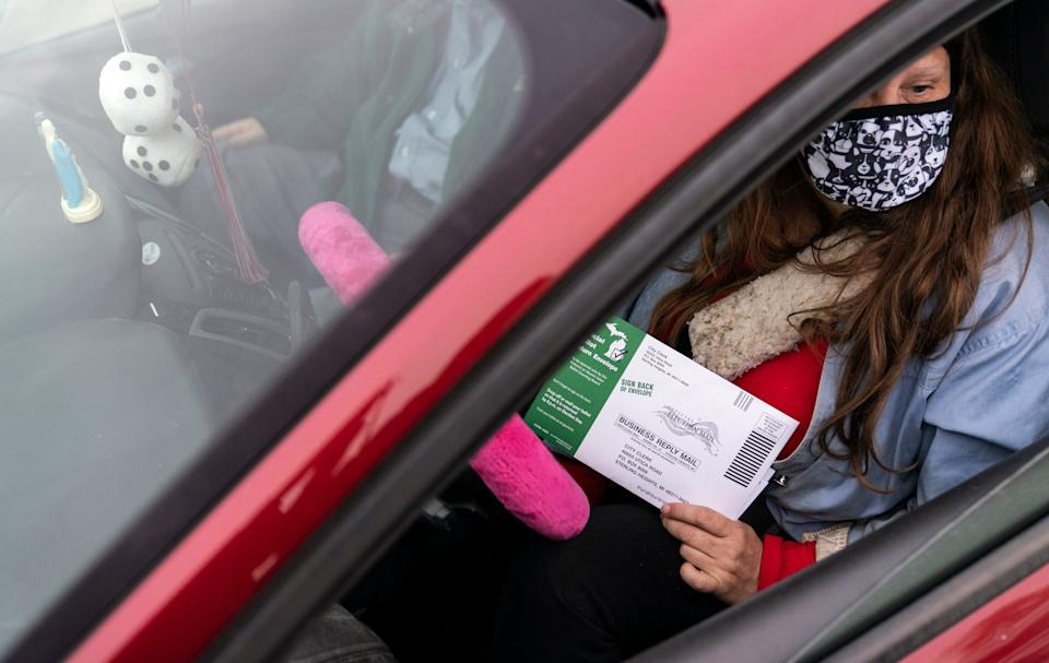 Jane Fisher holds her absentee ballot while waiting in her car with her brother, Anthony, for the doors to open to the Election Center for absentee early voting for the general election in Sterling Heights, Mich., Thursday, Oct. 29, 2020. (AP Photo/David Goldman) ORG XMIT: MIDG104