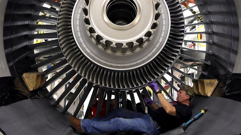 A GE Aviation employee lying on his back, building a massive engine.