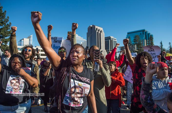 Veronica Curry, front with hoop earrings, raises her fist with other Black Lives Matter supporters.