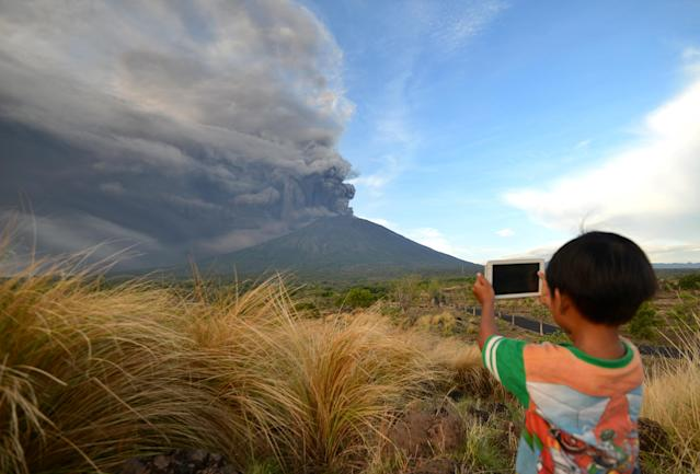 <p>A boy takes pictures during Mount Agung's eruption seen from Kubu sub-district in Karangasem Regency on Indonesia's resort island of Bali on Nov. 26, 2017. (Photo: Sonny Tumbelaka/AFP/Getty Images) </p>