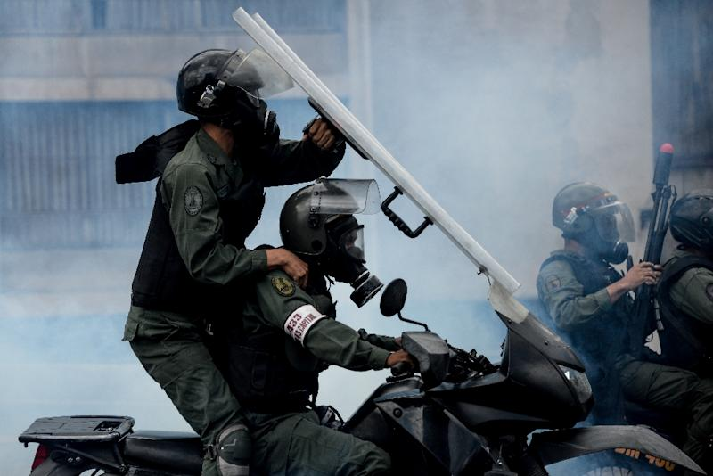 Riot police confront demonstrators during clashes which erupted during a march against President Nicolas Maduro in Caracas (AFP Photo/Federico PARRA)