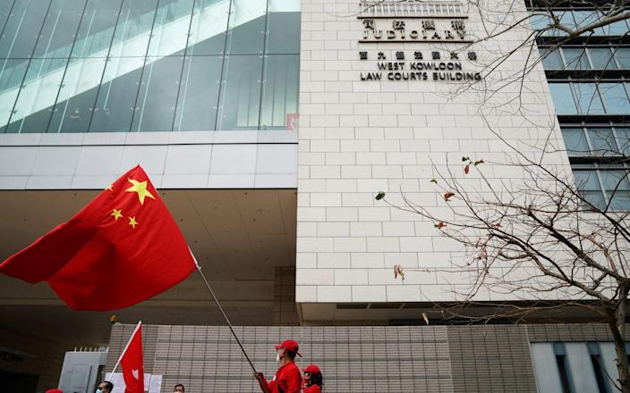 A pro-government supporter holds a Chinese flag outside a court in Hong Kong - Reuters