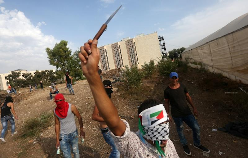 A Palestinian youth raises a knife during clashes with Israeli security forces (unseen) in the West Bank city of Tulkarem, on October 18, 2015 (AFP Photo/Jaafar Ashtiyeh)