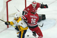 Carolina Hurricanes goaltender Alex Nedeljkovic (39) and center Vincent Trocheck (16) defend the goal against Nashville Predators defenseman Ryan Ellis (4) during the third period of an NHL hockey game in Raleigh, N.C., Saturday, April 17, 2021. (AP Photo/Gerry Broome)