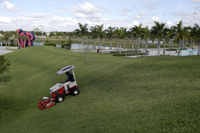 A worker mows the berm outside the Washington Nationals spring training baseball facility, Monday, March 16, 2020, in West Palm Beach, Fla. (AP Photo/Julio Cortez)