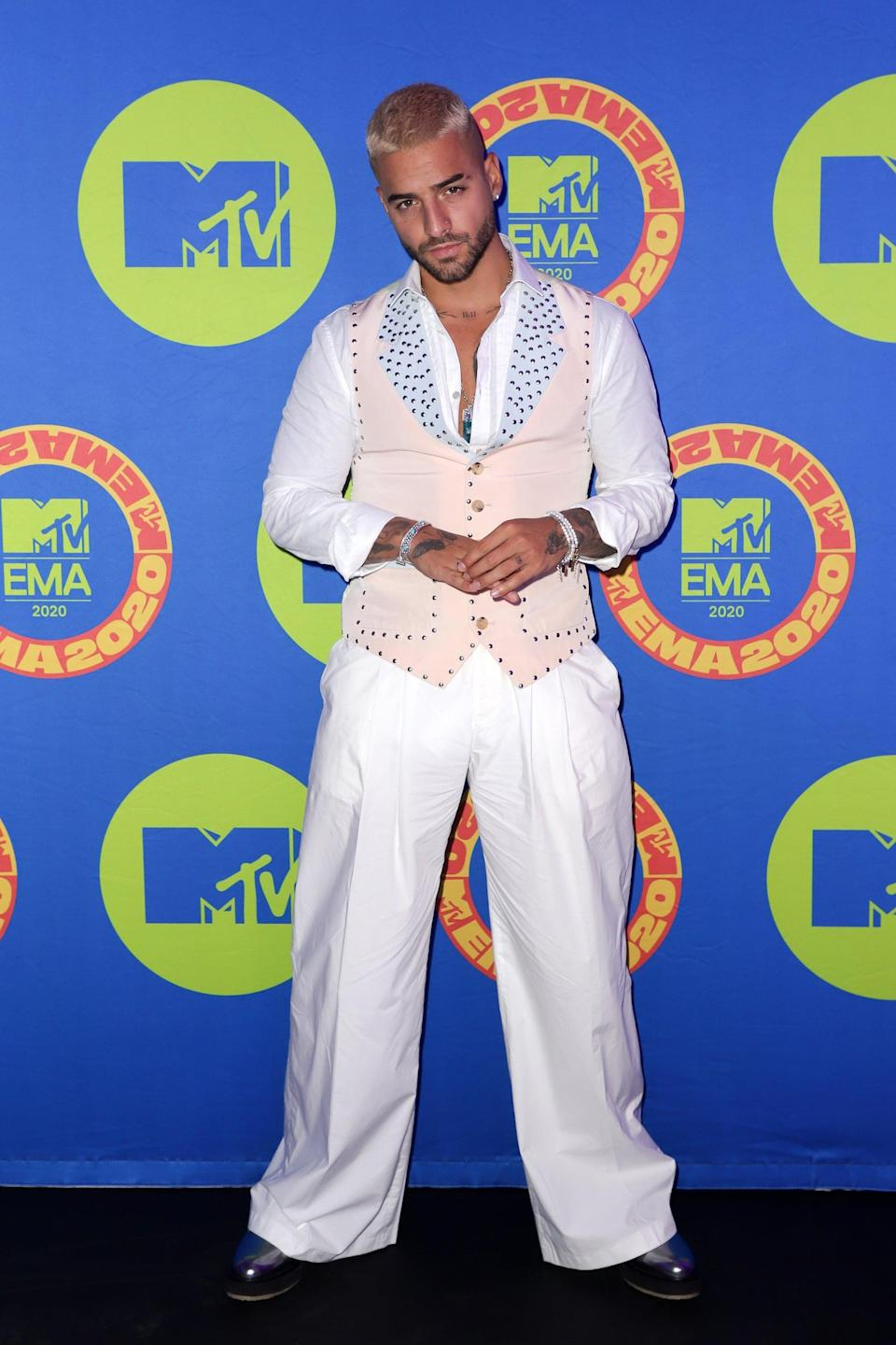 <p>Maluma wears a white shirt and trousers with a light-pink studded vest.</p>