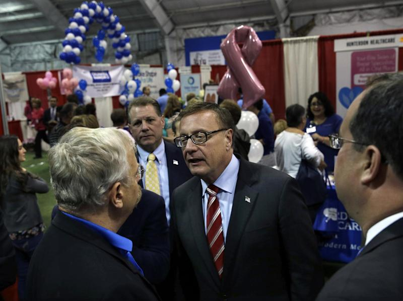 Republican candidate for Senate Steve Lonegan, center right, striped tie, greets people in Flemington, N.J., Tuesday, Oct. 15, 2013, as he campaigns for Senate at a trade show. Lonegan is running against Democratic Newark Mayor Cory Booker in Wednesday's election. Cory Booker's path to Wednesday's U.S. Senate election has been bumpier than anticipated. Even Republicans had expected Booker, a Democrat in a Democratic-leaning state, to cruise to victory over little-known Steve Lonegan. But the charismatic Newark mayor has faced sustained Republican criticism that has exposed vulnerabilities that could hamper him should he seek higher office someday. (AP Photo/Mel Evans)