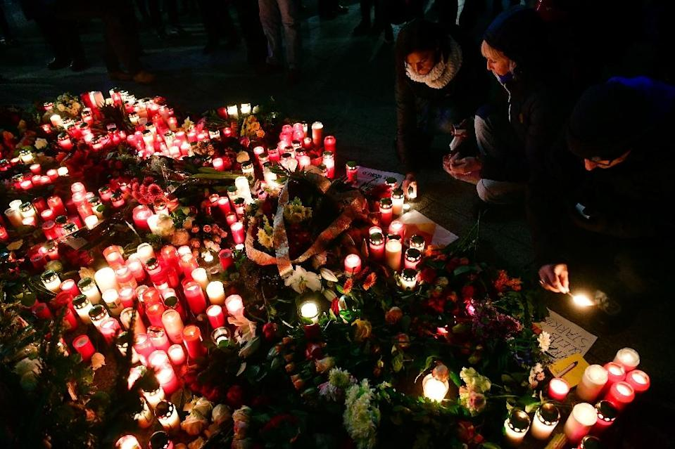 People light candles on December 20, 2016 at a makeshift memorial in front of the Kaiser-Wilhelm-Gedaechtniskirche in Berlin, where a truck crashed the day before into a Christmas market (AFP Photo/John MACDOUGALL)