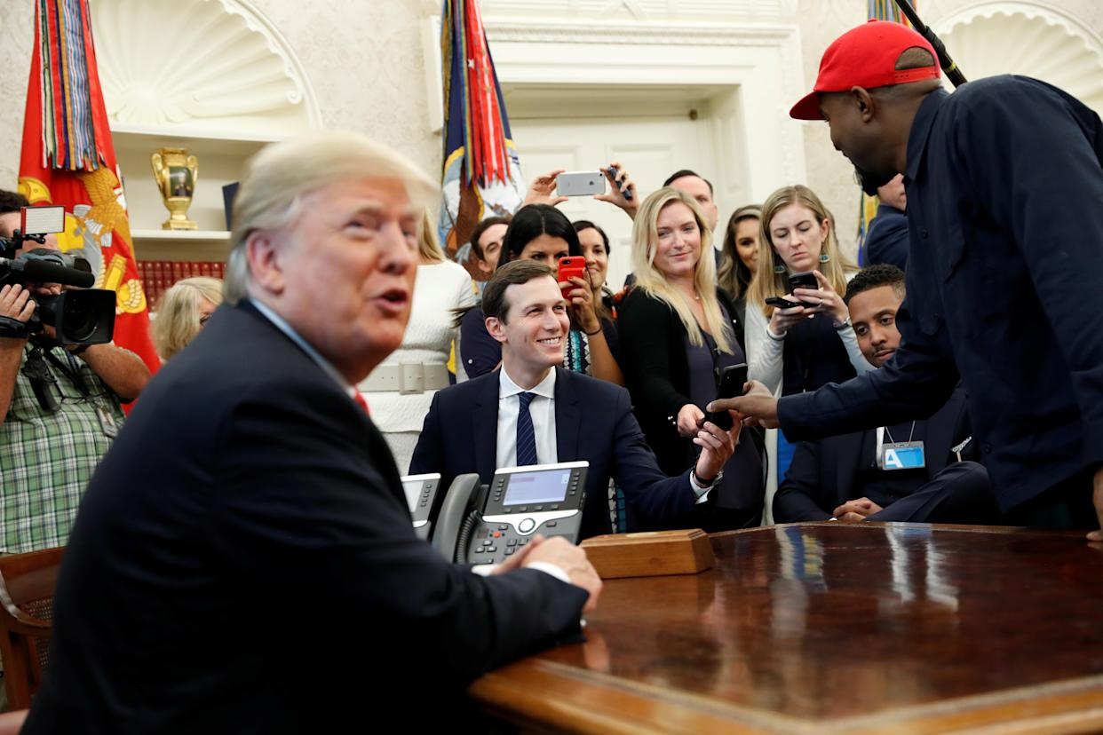 Kanye West shows a photo on his mobile phone to White House senior adviser Jared Kushner during a White House meeting with President Trump, Oct. 11, 2018. (Photo: Kevin Lamarque/Reuters)
