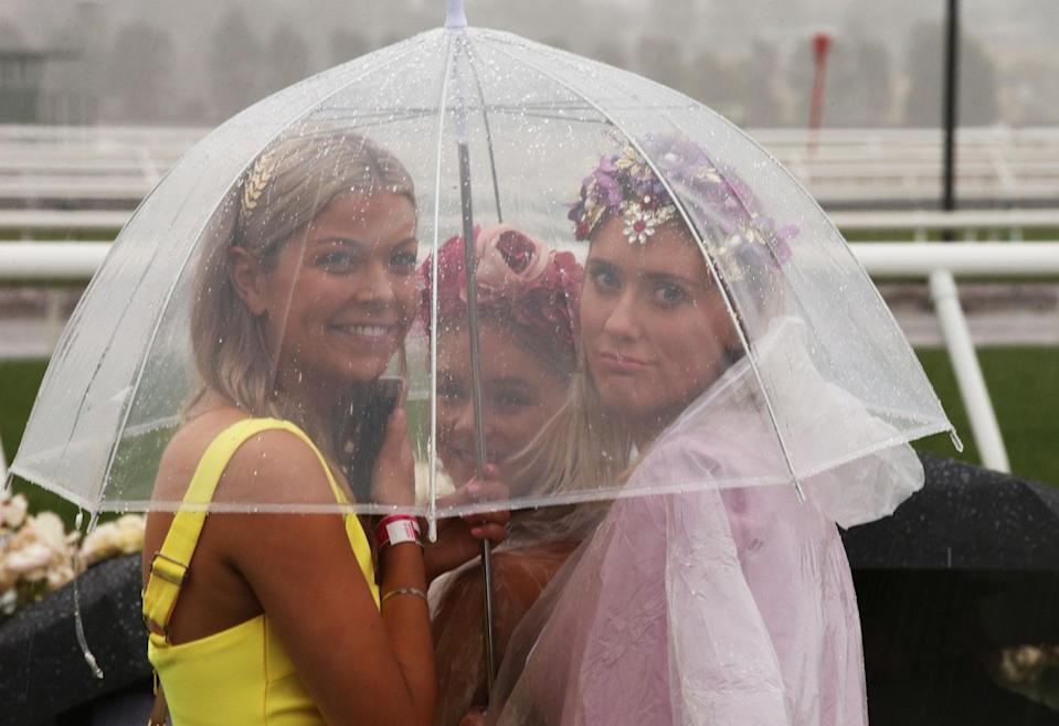 Some made the most of the downpour by smiling from underneath a clear umbrella. Photo: AAP