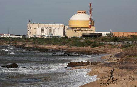 FILE PHOTO: A policeman walks on a beach near Kudankulam nuclear power project in the southern Indian state of Tamil Nadu