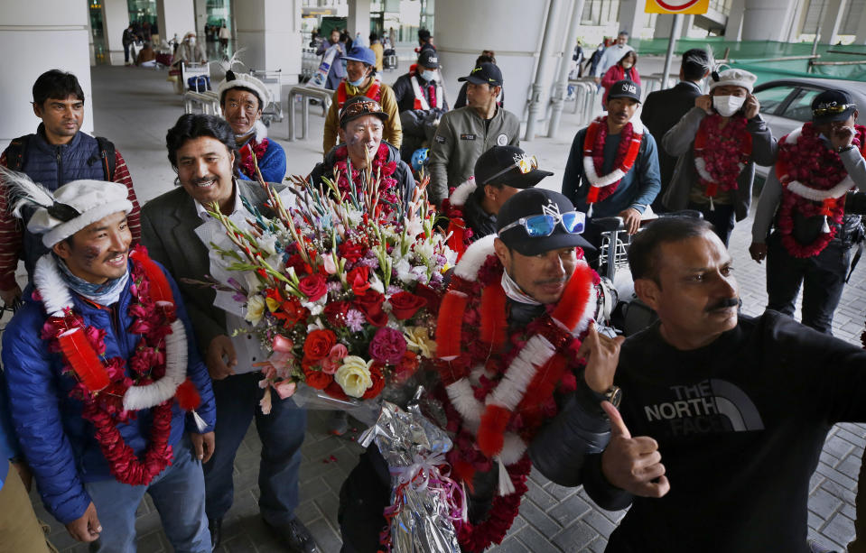 Nepalese climber Nirmal Purja, second right, and his team, who recently made history by scaling the K2 summit in the winter season, pose for a selfie with local tour operators upon their arrival at airport in Islamabad, Pakistan, Thursday, Jan. 21, 2021. Winter winds on K2 can blow at more than 200 km per hour (125 miles per hour) and temperatures can drop to minus 60 C (minus 76 F), an official of Pakistan's Alpine Club, Karrar Haideri said. (AP Photo/Anjum Naveed)