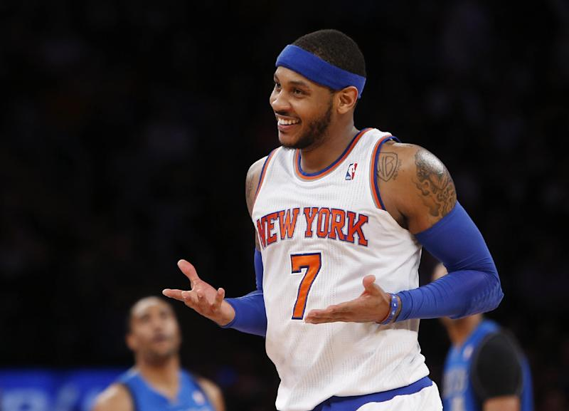 """In this Feb. 24, 2014, file photo, New York Knicks' Carmelo Anthony (7) smiles after hitting a 3-point shot against the Dallas Mavericks during an NBA basketball gam in New York. Anthony is remaining with the Knicks, saying he wants """"to stay and build here with this city and my team."""" Anthony made his decision official Sunday with a posting on his website. He writes: """"In the end, I am a New York Knick at heart."""""""