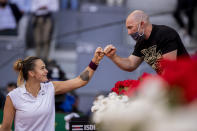 Aryna Sabalenka of Belarus, left, celebrates with her coach after winning the women's final match against Australia's Ashleigh Barty at the Mutua Madrid Open tennis tournament in Madrid, Spain, Saturday, May 8, 2021. (AP Photo/Bernat Armangue)