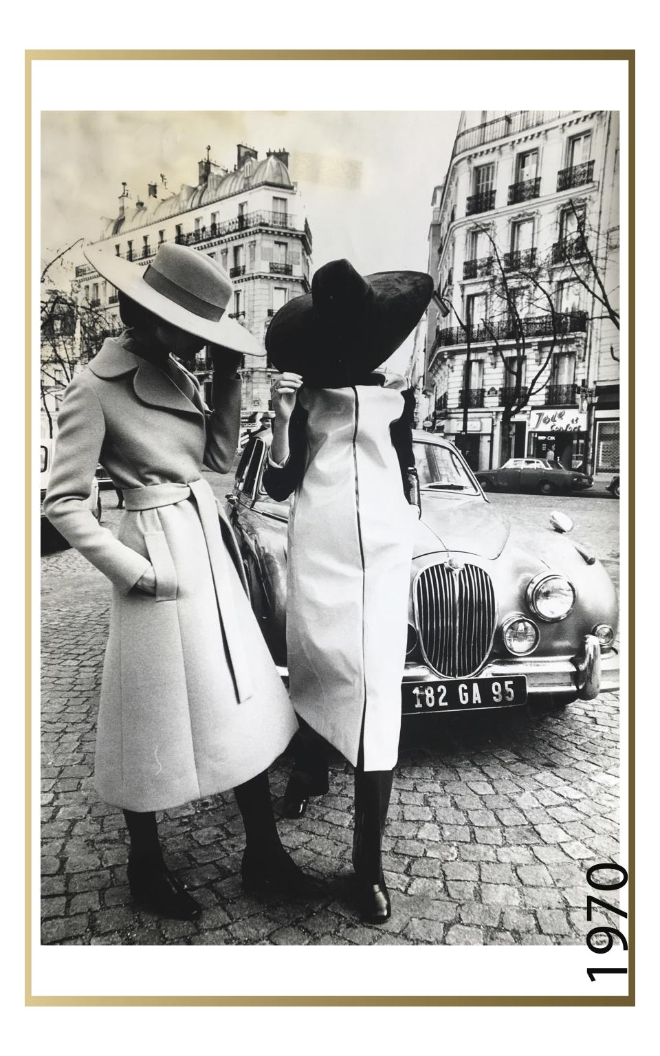 Two models posing on the streets of Paris, in large-brimmed suede and felt hats, paired with a belted, wool, knee-length coat and a vinyl, knee-length, raincoat, over dark-colored pants and shoes, from the Jay Jaxon spring 1970 collection for Maison Jean-Louis Scherrer, 1970. - Credit: Photographer Unknown, Editorial Image, 1970, Maison of Jean-Louis Scherrer, Jay Jaxon's Portfolio, Bequest of Lloyd Hardy, Rachel Fenderson Collection, 2017