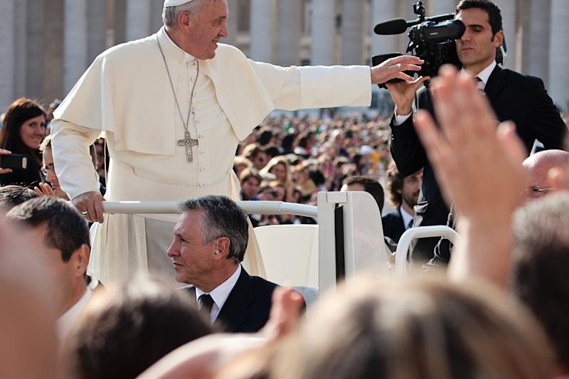 Vatican City State - October 30, 2013: Pope Francis I on the popemobile blesses the faithful crowd in St. Peter's Square in Vatican.