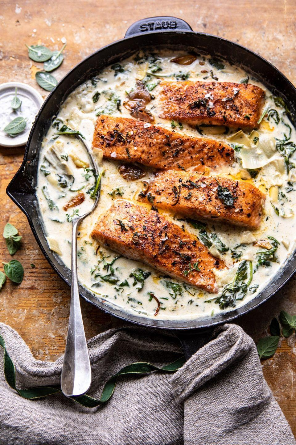 """<p>You can whip up this creamy, buttery salmon dish in just over a half hour. The best part is that it tastes <em>just</em> like spinach and artichoke dip.</p><p><strong>Get the recipe at <a href=""""https://www.halfbakedharvest.com/creamy-spinach-and-artichoke-salmon/"""" rel=""""nofollow noopener"""" target=""""_blank"""" data-ylk=""""slk:Half Baked Harvest"""" class=""""link rapid-noclick-resp"""">Half Baked Harvest</a>.</strong></p><p><strong><strong><a class=""""link rapid-noclick-resp"""" href=""""https://www.amazon.com/Seasoned-Cast-Skillet-Utopia-Kitchen/dp/B00X4WQMAS?tag=syn-yahoo-20&ascsubtag=%5Bartid%7C10063.g.35055779%5Bsrc%7Cyahoo-us"""" rel=""""nofollow noopener"""" target=""""_blank"""" data-ylk=""""slk:SHOP CAST IRON SKILLETS"""">SHOP CAST IRON SKILLETS</a></strong><br></strong></p>"""