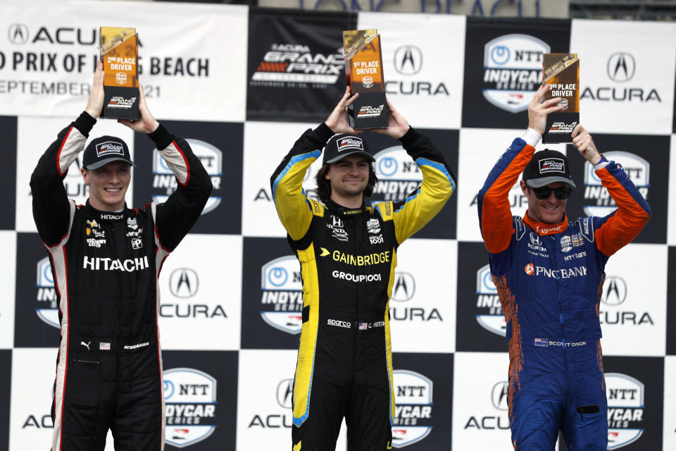 Driver Colton Herta, center, holds up his first place trophy for photographers with second place winner Josef Newgarden, left, and third place winner Scott Dixon, right, during an IndyCar auto race at the Grand Prix of Long Beach, Sunday, Sept. 26, 2021, in Long Beach, Calif. (AP Photo/Alex Gallardo)
