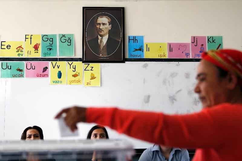 A Turkish Cypriot woman casts her vote at a polling station in the eastern port city of Famagusta in front of a portrait of Mustafa Kemal Ataturk, the founder of modern Turkey, during the second round of the presidential elections on April 26, 2015 (AFP Photo/Florian Choblet)