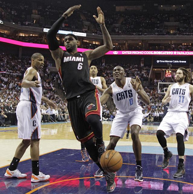 Miami Heat's LeBron James (6) is fouled as he drives past Charlotte Bobcats' Bismack Biyombo (0) during the first half in Game 4 of an opening-round NBA basketball playoff series in Charlotte, N.C., Monday, April 28, 2014. (AP Photo/Chuck Burton)