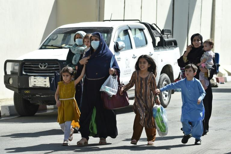 Afghan woman with children, hoping to leave Afghanistan, walk through the main entrance gate of Kabul airport on August 28, 2021 as the US military prepared to leave (AFP/WAKIL KOHSAR)