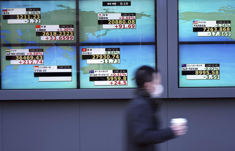 A man walks past an electronic stock board showing Japan's Nikkei 225 index and other country's index at a securities firm in Tokyo Monday, Feb. 4, 2019. Asian markets were mixed Monday as traders questioned an imminent meeting between American and Chinese officials to work on disagreements ranging from technology development to trade. (AP Photo/Eugene Hoshiko)