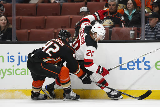 New Jersey Devils' Blake Coleman, right, is defended by Anaheim Ducks' Josh Manson during the first period of an NHL hockey game Sunday, March 18, 2018, in Anaheim, Calif. (AP Photo/Jae C. Hong)