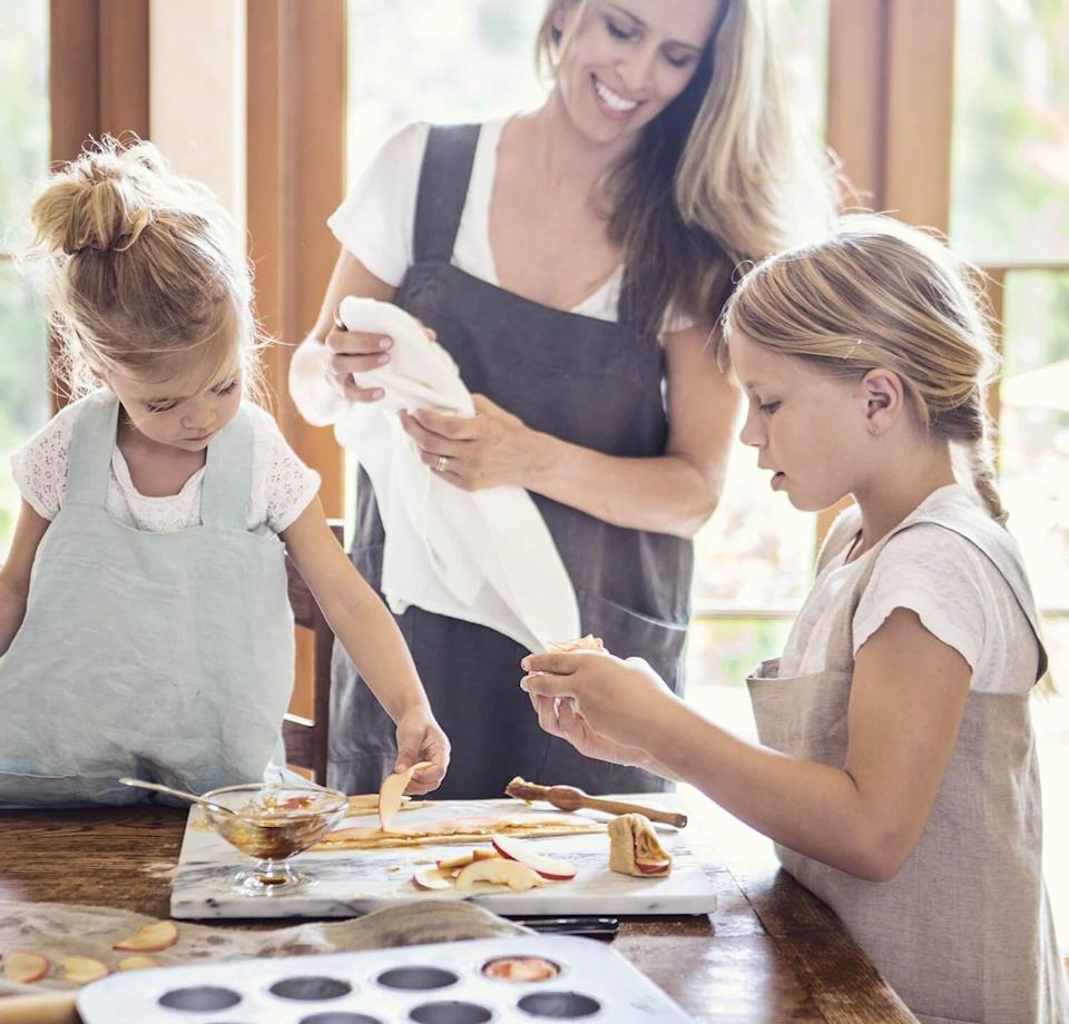 "<p>This accessory will come in handy, whether they're teaching ""home ec"" cooking or arts and crafts. Handmade in California, the artisanal apron has a wrap-around design that protects the front as well as the back with two comfortable crossover straps that don't pull at the neck like a traditional one.</p> <p><strong><em>Shop Now: </em></strong><em>Rough Linen The Original Linen Pinafore Apron, $85, </em><a href=""https://www.roughlinen.com/collections/linen-aprons-pinafores/products/linen-pinafore"" rel=""nofollow noopener"" target=""_blank"" data-ylk=""slk:roughlinen.com"" class=""link rapid-noclick-resp""><em>roughlinen.com</em></a><em>.</em></p>"