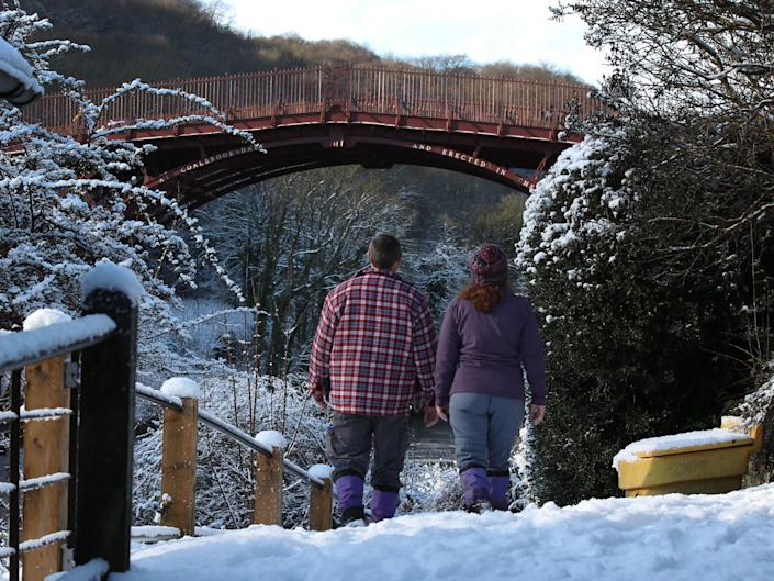 A couple walk in the snow to look at The Iron Bridge in the town of Ironbridge, Shropshire (PA)